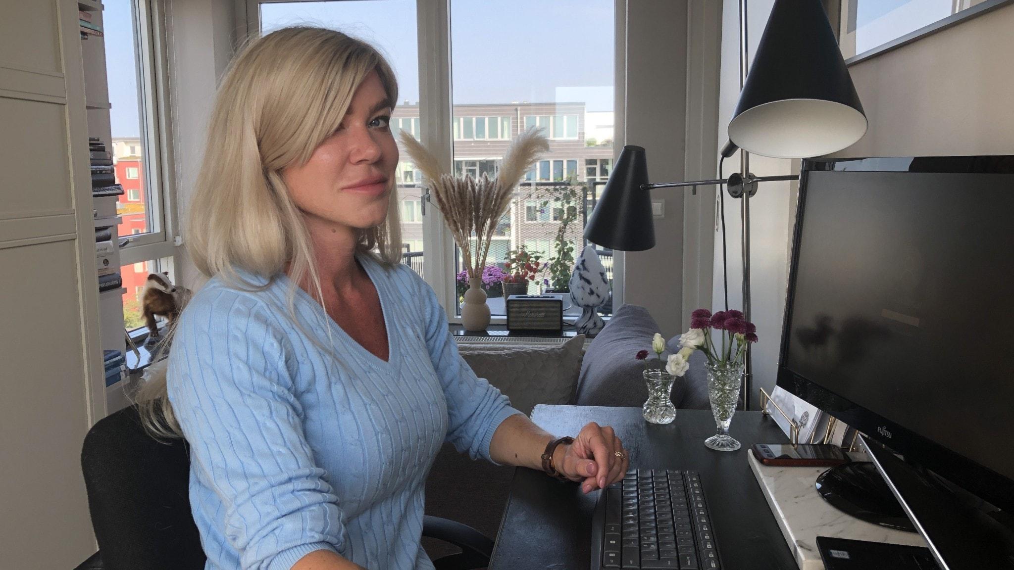En kvinna sitter vid en datorskärm vid ett skrivbord i sin lägenhet. I bakgrunden syns utsikten genom fönster med blå himmel.