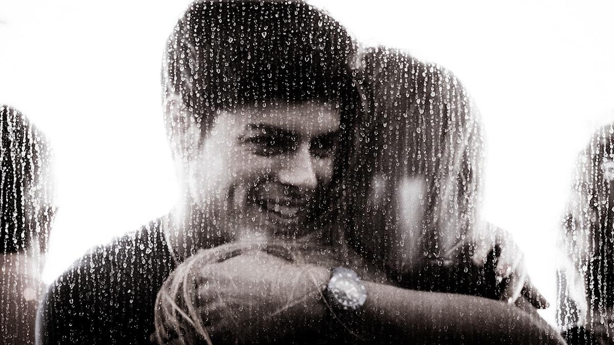 En ung man kramar om någon bakom ett regnigt fönster