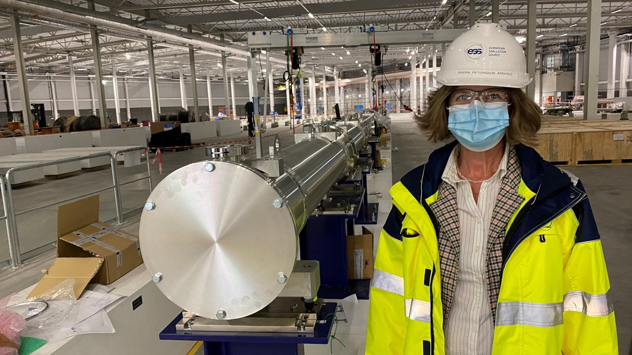 En kvinna står med bygghjälm, munskydd och neongul arbetsjacka i en stor hangarliknande byggnad, vid sidan om ett stort långt metallrör.