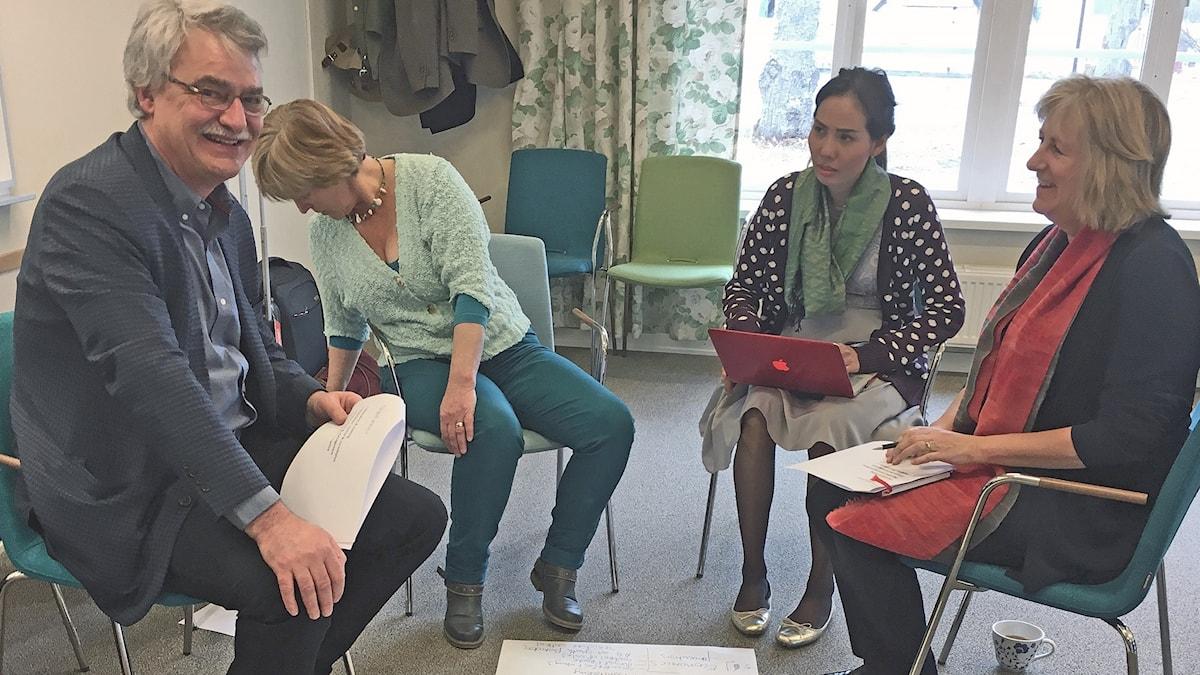 Fyra sitter på stolar och diskuterar