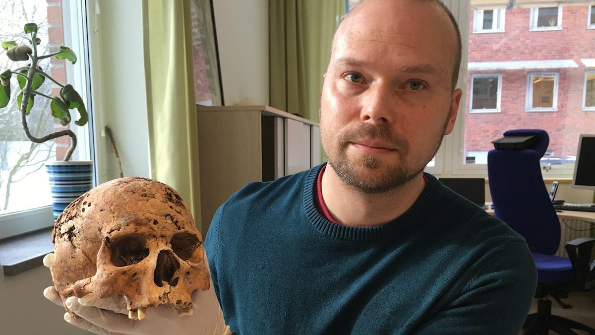 Mattias Jakobsson håller i ett skelett