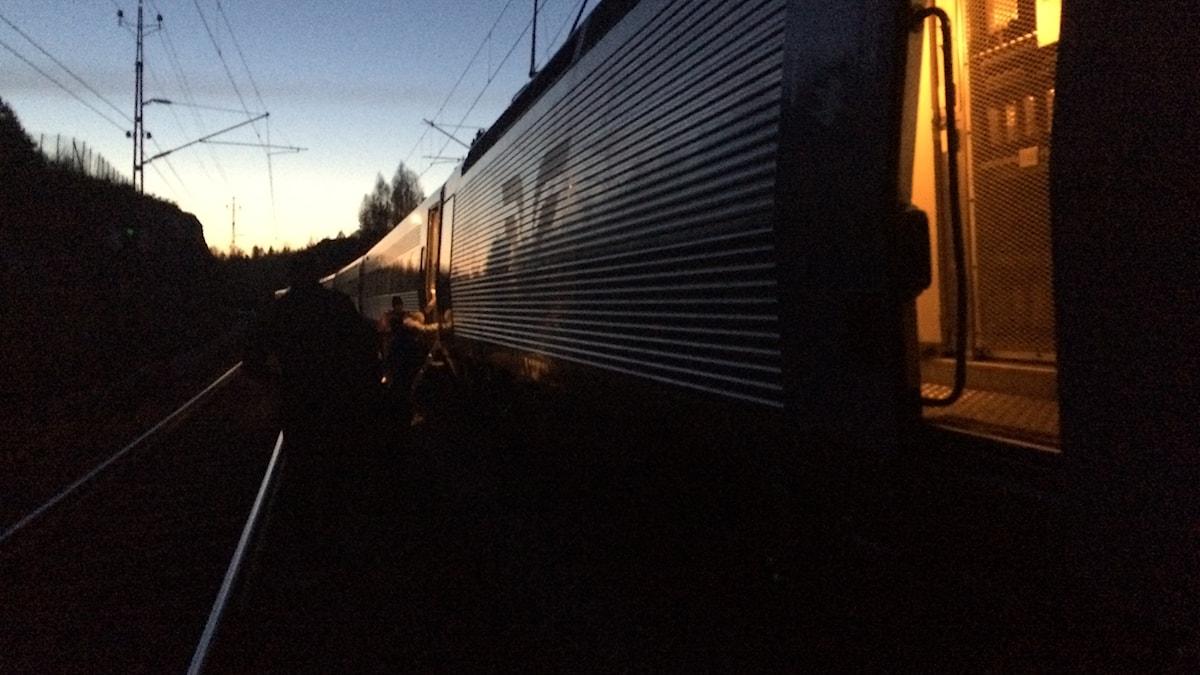 ett tåg står stilla på en räls i soluppgången