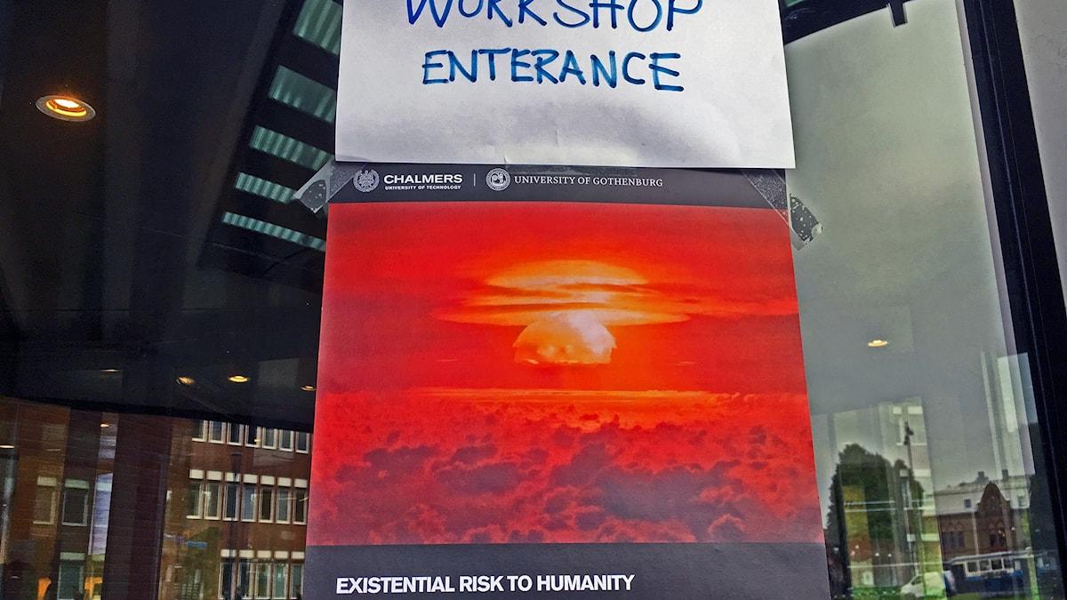 """En affisch med en bild på en atombomb. Över det en skylt """"workshop entrance"""""""