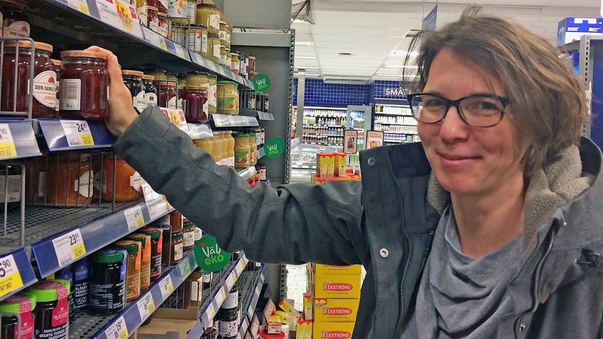 Annika Wallin håller en burk i butikshylla