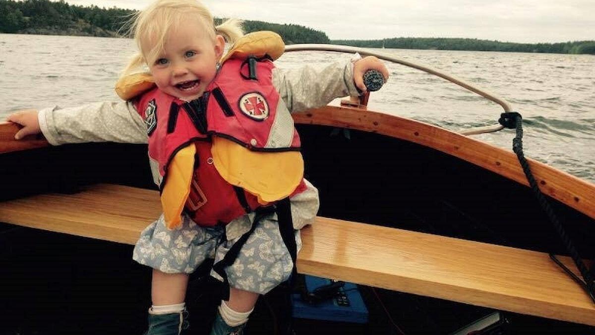 Liten tjej styr en båt