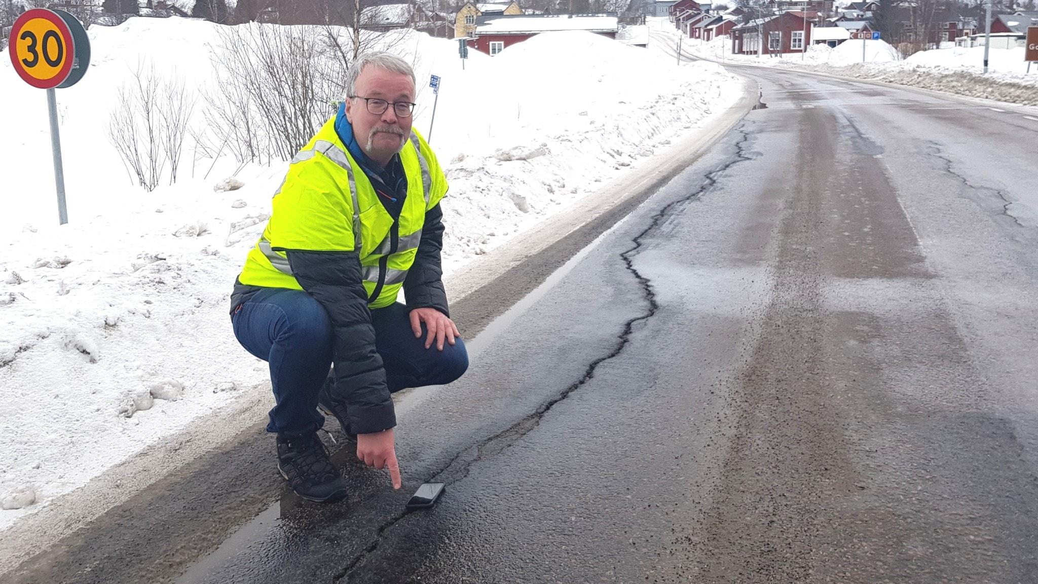 Johan Ullberg vid Trafikverket visar på en tjälspricka i asfalten.