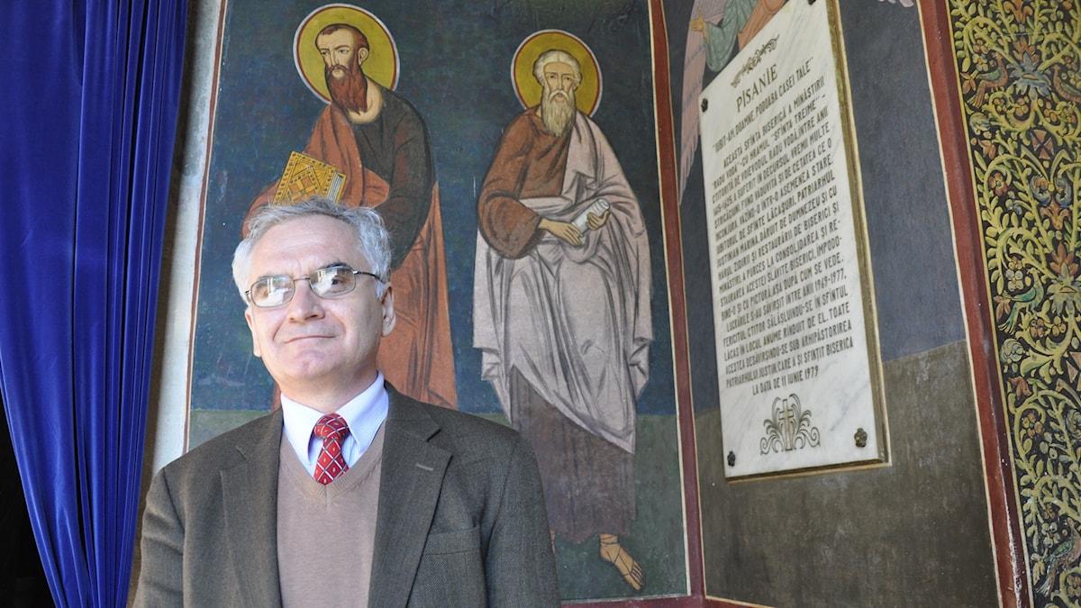 Historikern Viorel Achim framför en väggmålning i klostret Radu Voda.