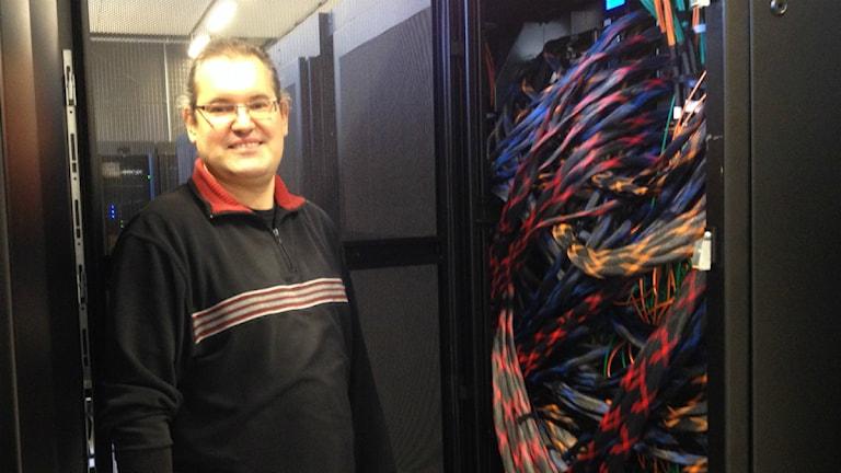 Erwin Laure visar några av superdatorn Beskows kablar. Foto: Karin Gyllenklev.
