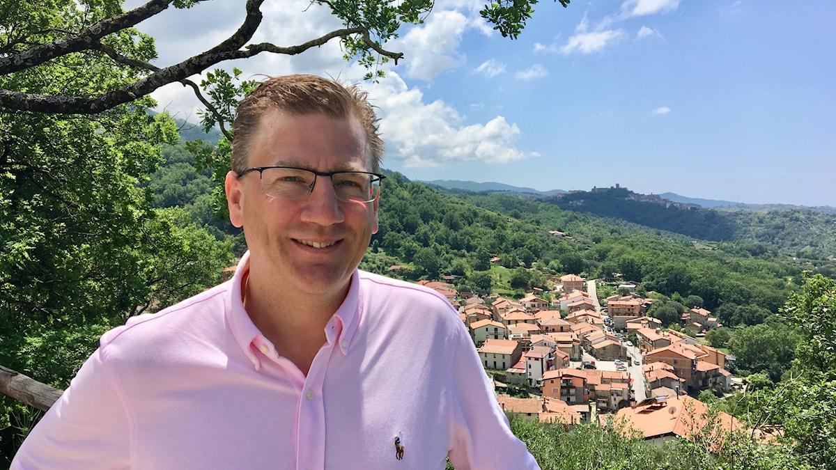Forskaren Olle Melander framför vacker utsikt av italienska berg.