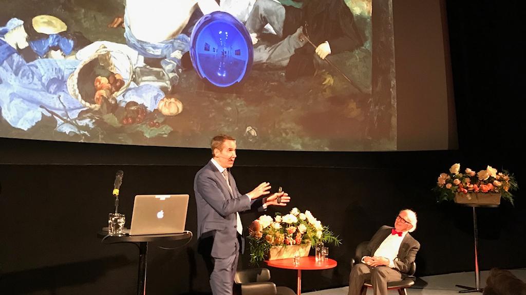 """Jeff Koons samtalar med Eric Kandel. I bakgrunden""""Frukost i det gröna"""" med en av hans blå spegelklot mitt i picknicken."""