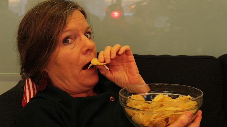 En kvinna sitter med en skål med chips och är just på väg att stoppa ett par i munnen. Hon tittar mot kameran och ser orolig ut. Kvinnan är veckomagasinets programledare Lena Nordlund.