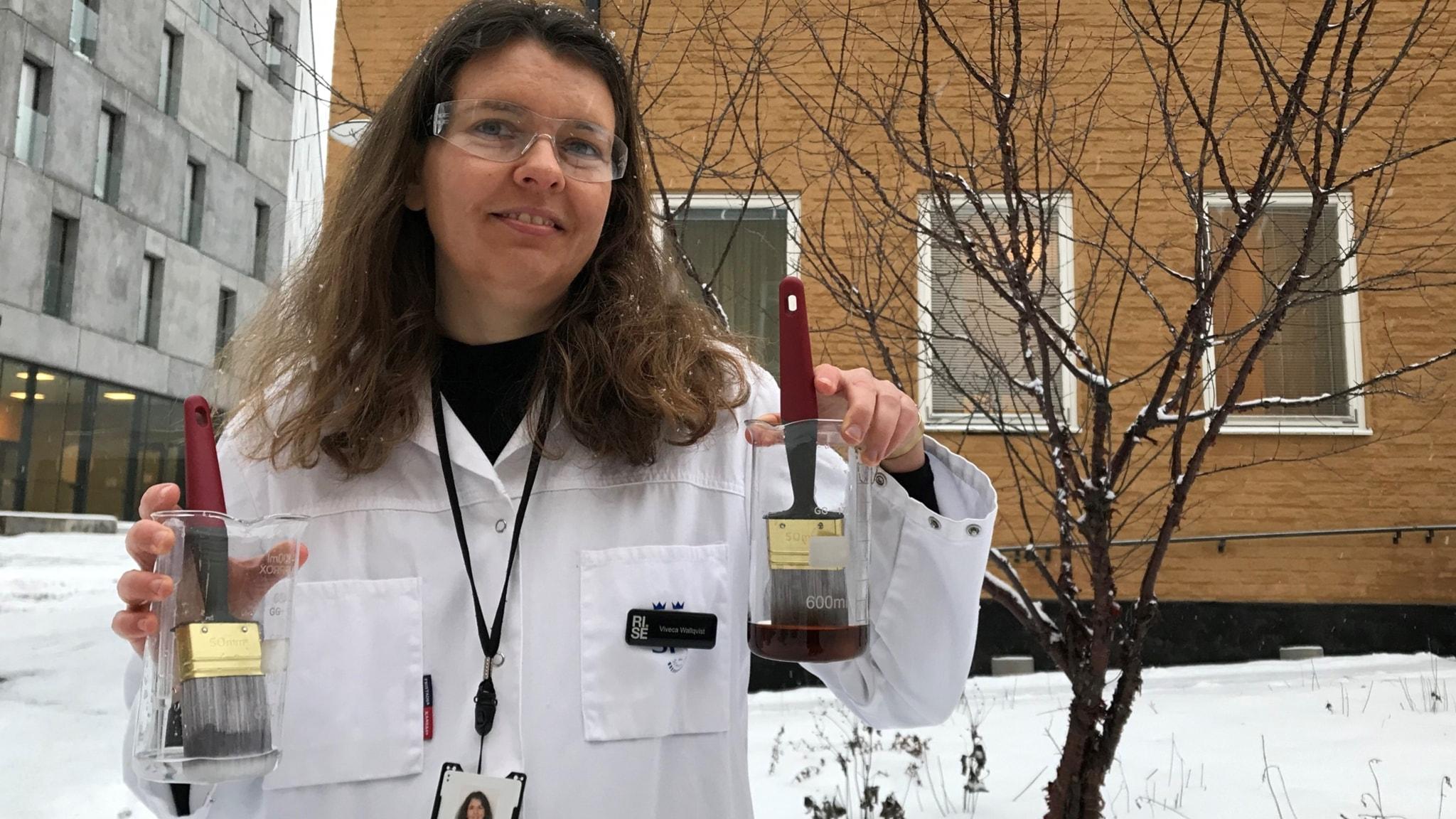 En kvinna står utomhus i vit labbrock. Hon tittar mot kameran och håller upp två glasburkar med en pensel i vardera burken.