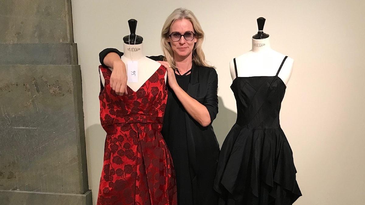 En kvinna med tonade glasögon står i svart klänning och tittar leende in i kameran. På vardera sidan om henne står en provdocka med en klänning på, en är röd, en är svart.