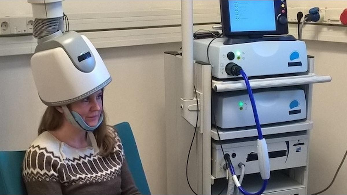 Magdalena Barnekow med en hårtorksliknande apparat på huvudet