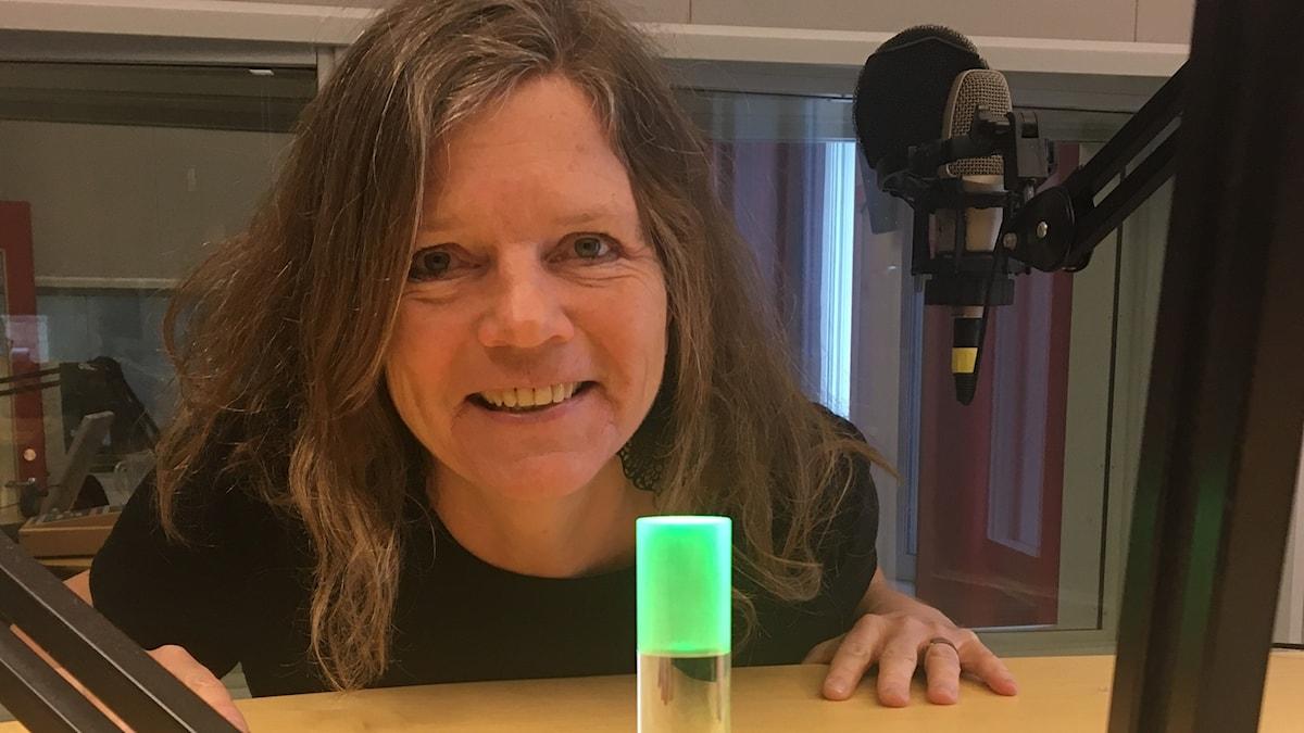 Programledaren Lena Nordlund i studion vid en grön lampa.