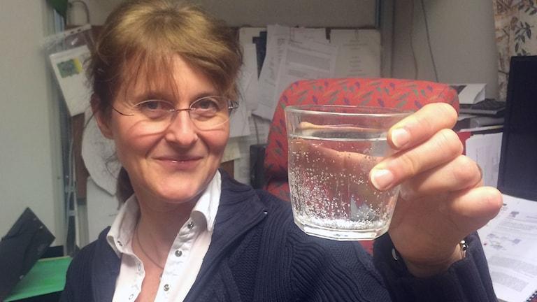 Forskaren Helena Grennberg håller upp ett glas med vatten.