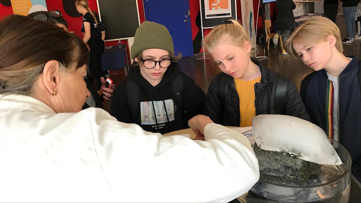 Tre barn står och tittar koncentrerat på ett par stycken is som ligger på ett bord. En kvinna med ryggen mot kameran visar dem något med isen.