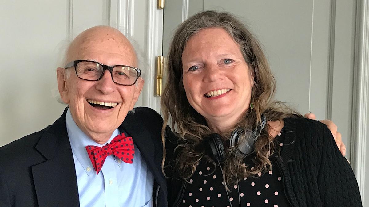 En äldre man med glasögon och röd fluga står och håller om programledaren Lena Nordlund. Båda ler stort.