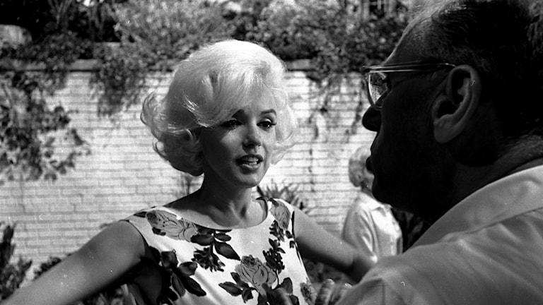 Marilyn Monroe diskuterar med regissören George Cukor under en filminspelning.