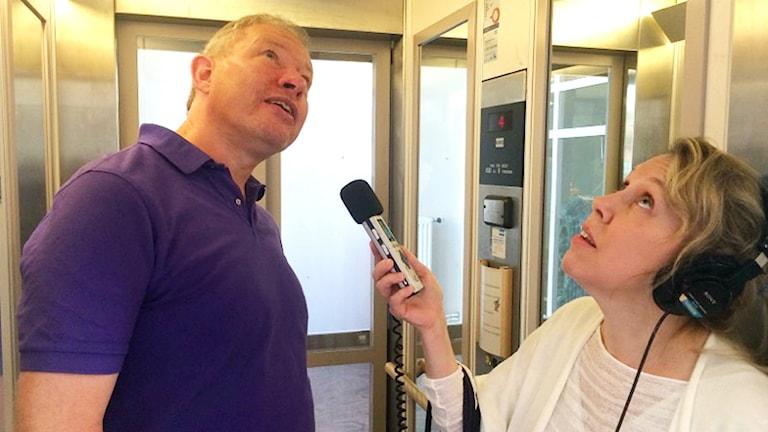 Fysikern Anders Eriksson intervjuas av reporter Lisen Forsberg i en hiss.