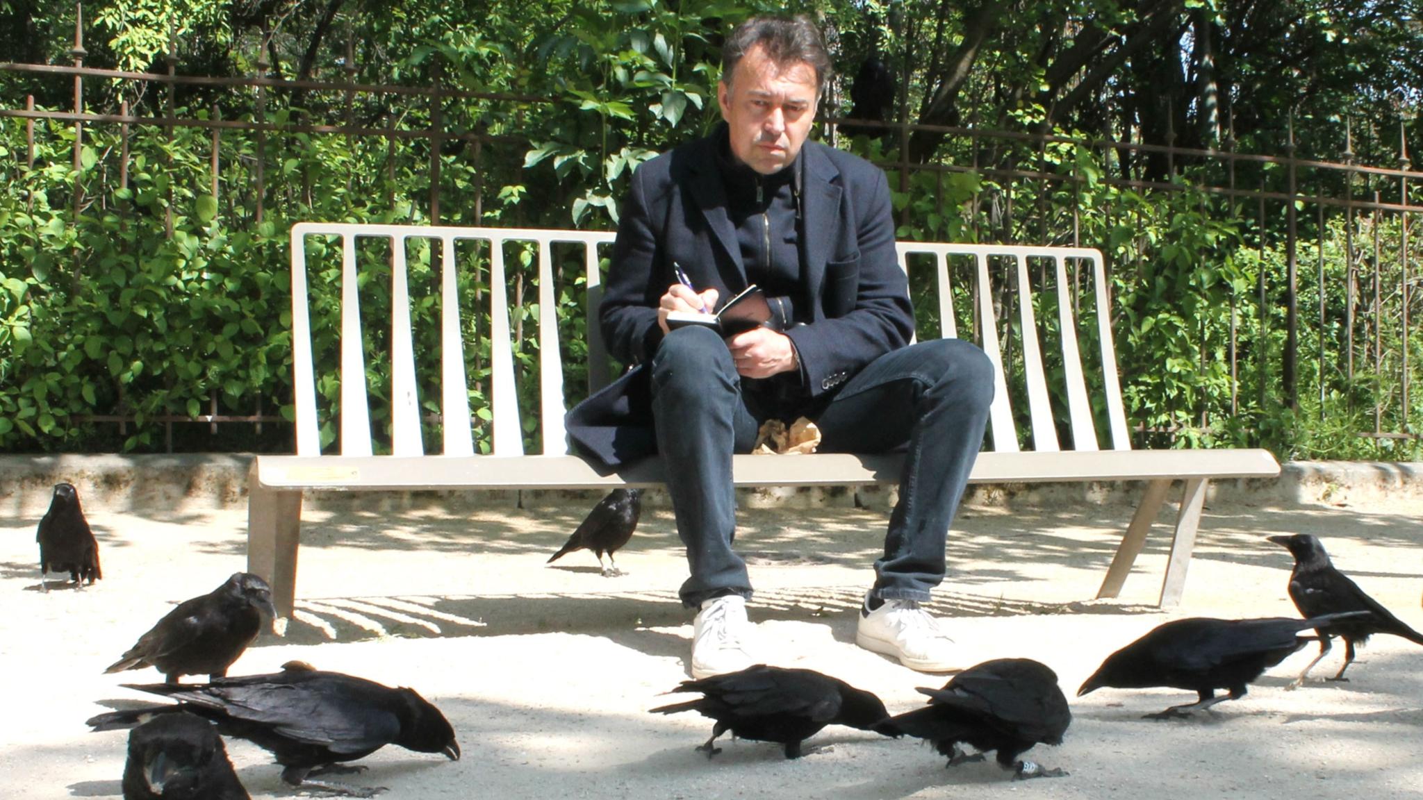 Ornitologen Frédéric Jiguet sitter på en parkbänk och observerar kråkor i Paris.