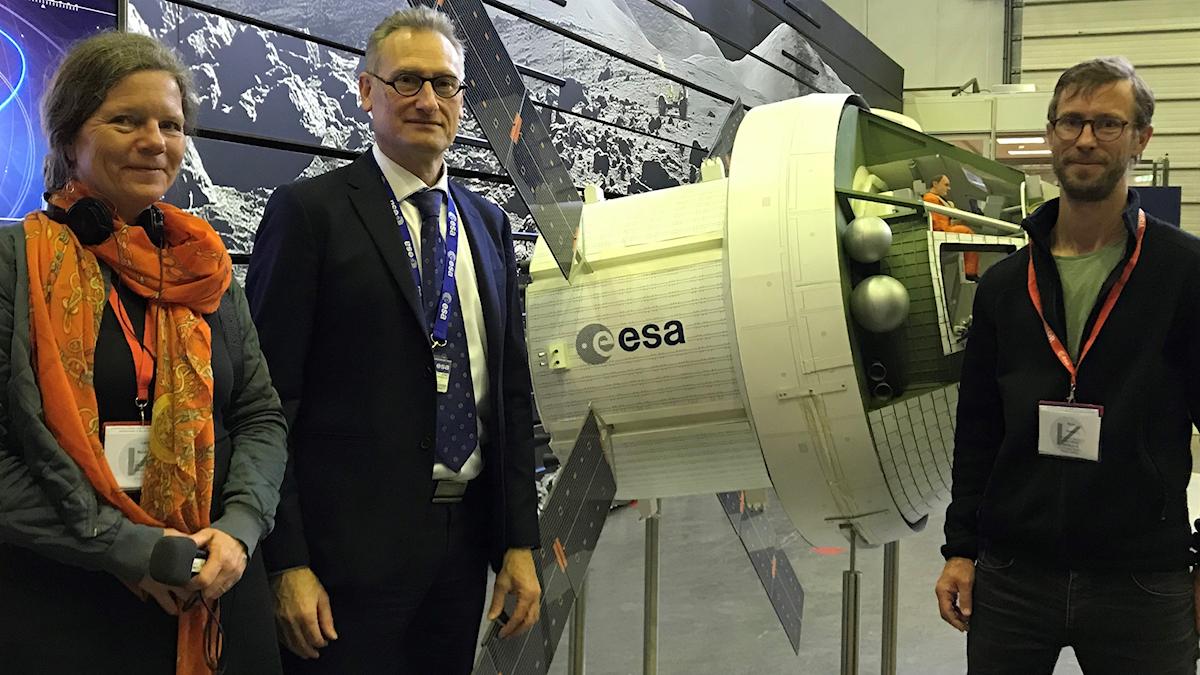 Vetenskapsradions reportrar står tillsammans med en chef från ESA intill en modell av en rymdkapsel.