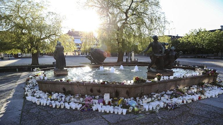 Blommor och ljus till minne av Lisa Holm vid fontänen Livets Brunn i Skövde. Foto: Björn Larsson Rosvall / TT