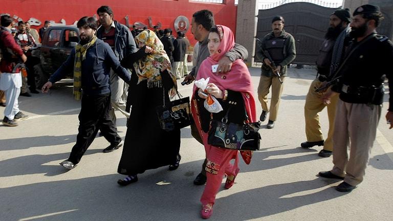Anställda vid Bacha Khan universitetet i Pakistan lämnar campus. Beväpnade män attackerade universitetet den 20 januari, 2016. Foto: AP