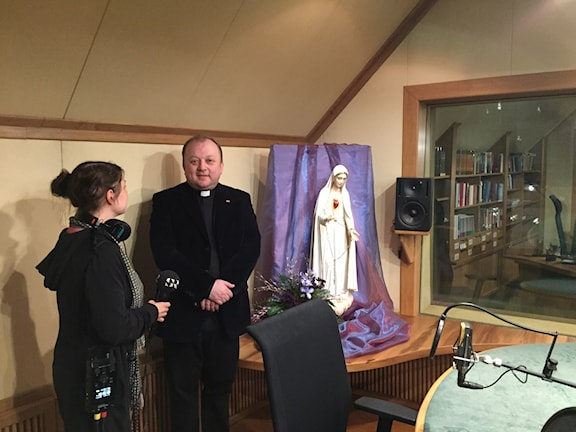 Prästen och radioprataren Fader Janusz Dyrek visar Radio Maryjas studio för Sveriges Radios korrespondent Thella Johnson.