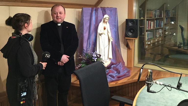 Prästen och radioprataren Fader Janusz Dyrek visar Radio Maryjas studio för vår  korrespondent Thella Johnson. Foto: Dorota Nygren