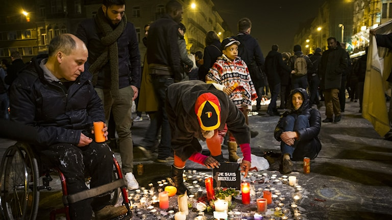 Människor samlas på Place de la Bourse i Bryssel för att tända ljus och minnas offren