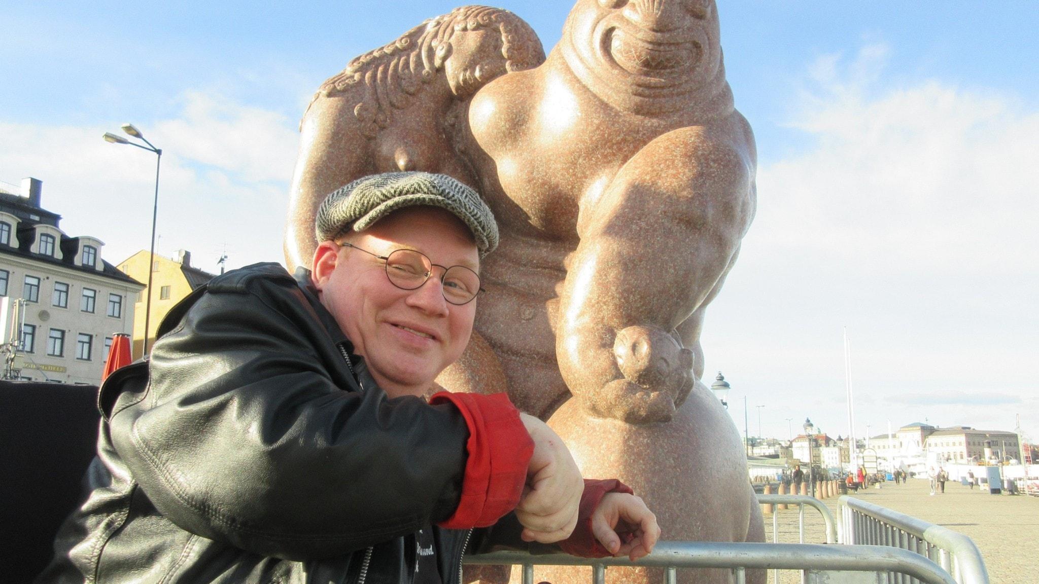 """Ante Blomberg med Carl Milles staty """"Sjöguden"""" på Skeppsbron i Stockholm."""
