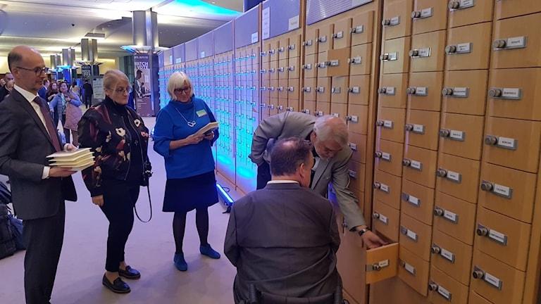 """Björn Tunbäck, Britt Stakston, Elisabeth Löfgren och Lars Öbrink lägger - under överinseende av David Lega - Dawit Isaaks översatta bok """"Hopp"""" i EU-parlamentarikernas postfack"""