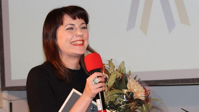 Charissa Martinkauppi mikki ja kukat käsissään. Foto: Irma-Liisa Pyökkimies / Sveriges Radio Sisuradio