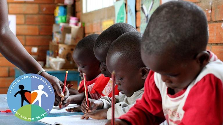 Barn skriver i ett klassrum i Uganda. Foto: Erikshjälpen.