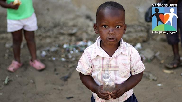 Världens barn i P4. Liten pojke med står med vattenflaska i handen i Moçambique.