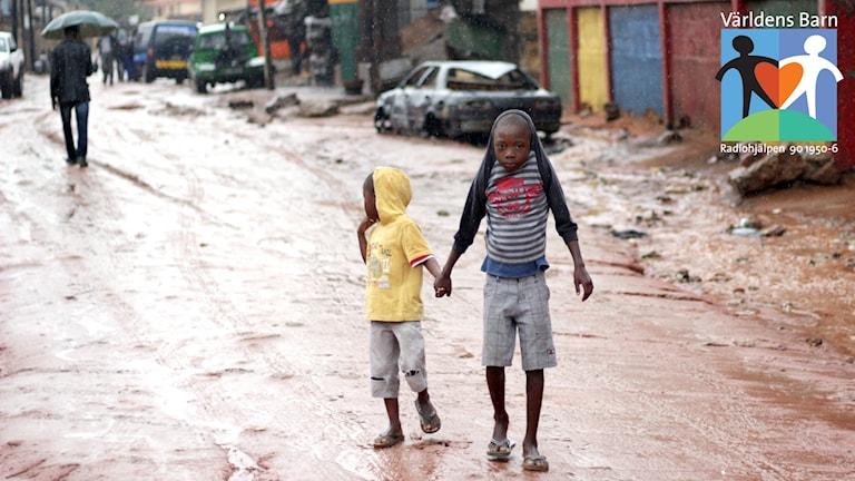 Världens barn i P4. Två pojkar går i regnet på en lerig gata i Moçambique.
