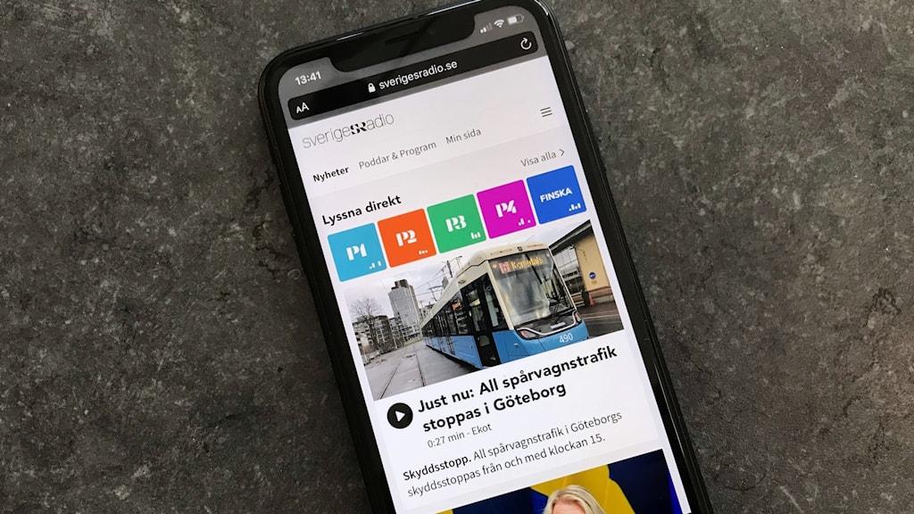 Mobiltelefon som visar Sveriges Radios sajt med ljudvågor i anslutning till direktlyssning.