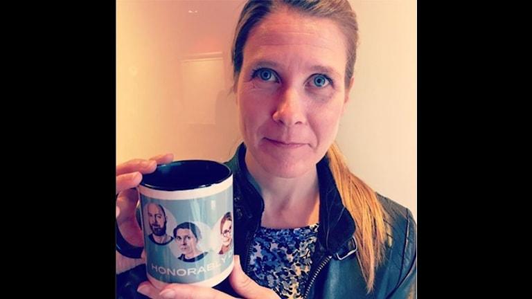 Kvinna som håller i kopp med sin bild på
