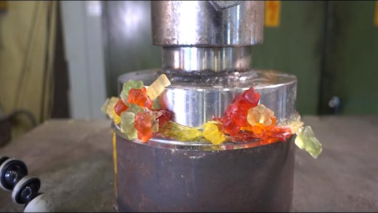 Bild på gummibjörnar som pressas i den hydrauliska pressen