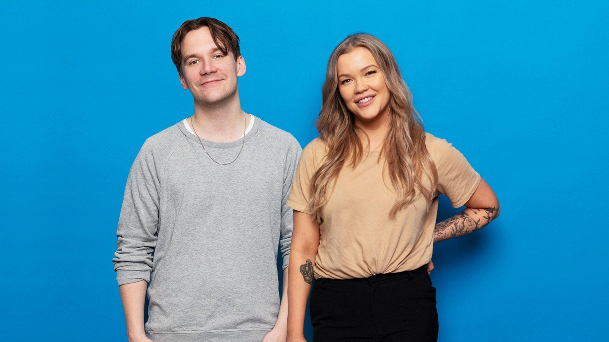 Pressbild på Isabelle och Christopher som står och ler framför en blå fotovägg.