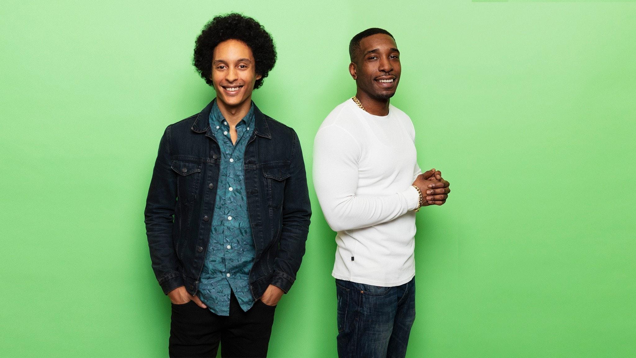 Victor Linnér och Ison Glasgow står framför en ljusgrön fondvägg och ler. Viktor har jeansskjorta och Ison har en vit tröja.