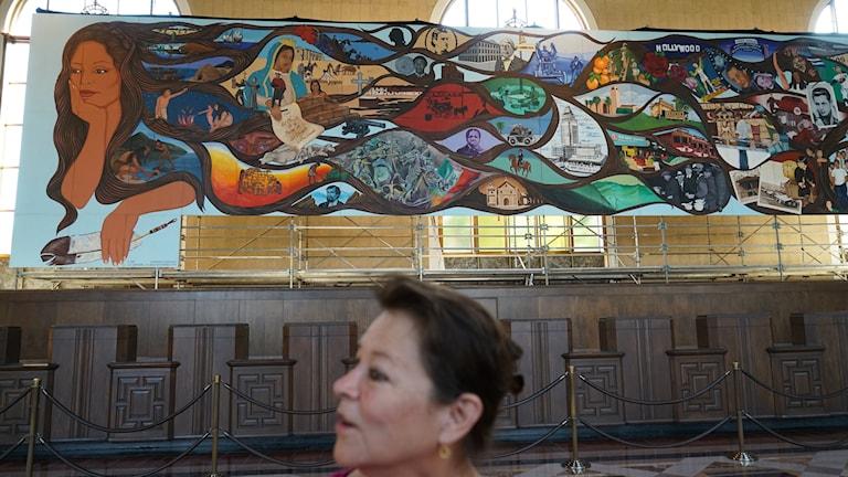Barbara Carrasco står framför sin muralmålning som fått ett tillfälligt hem på Los Angeles Union Station.