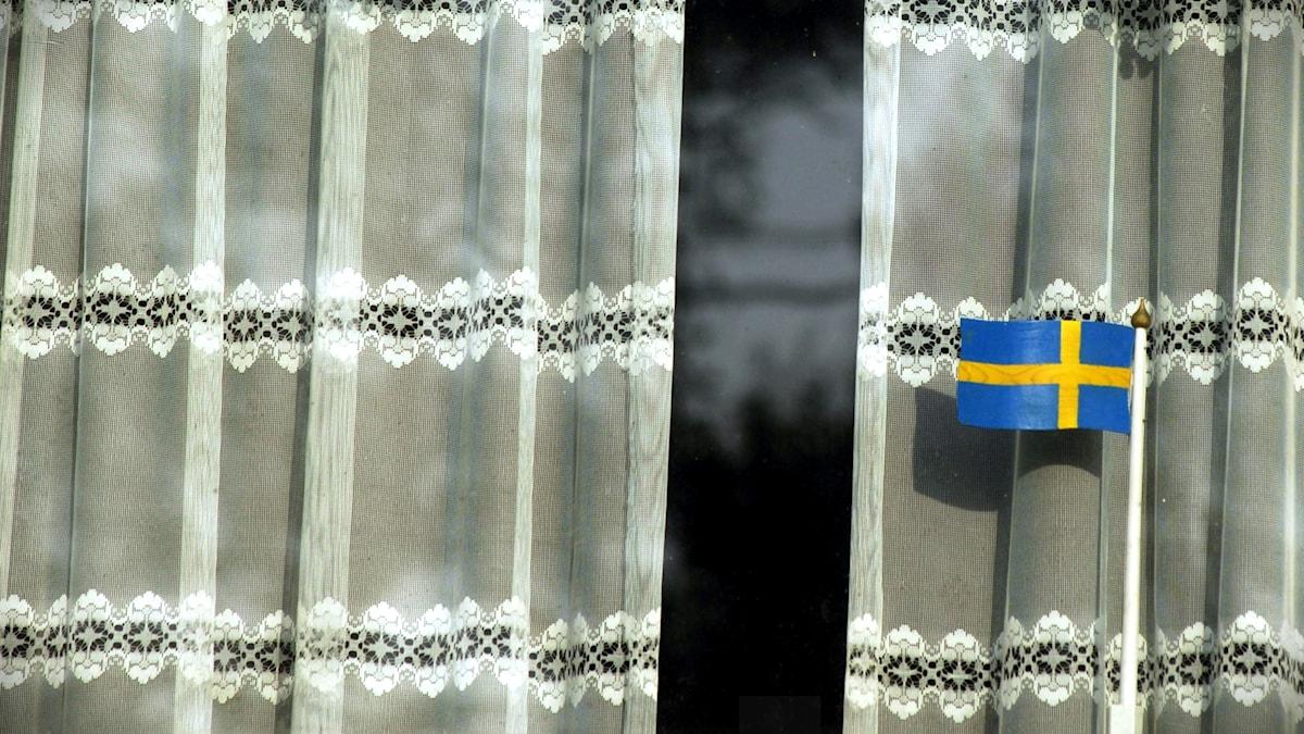 Svensk flagga i ett fönster med virkade gardiner.