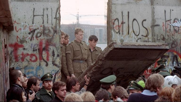 Demonstranter och gränsvakter när en bit av Berlinmuren fallit i november 1989.