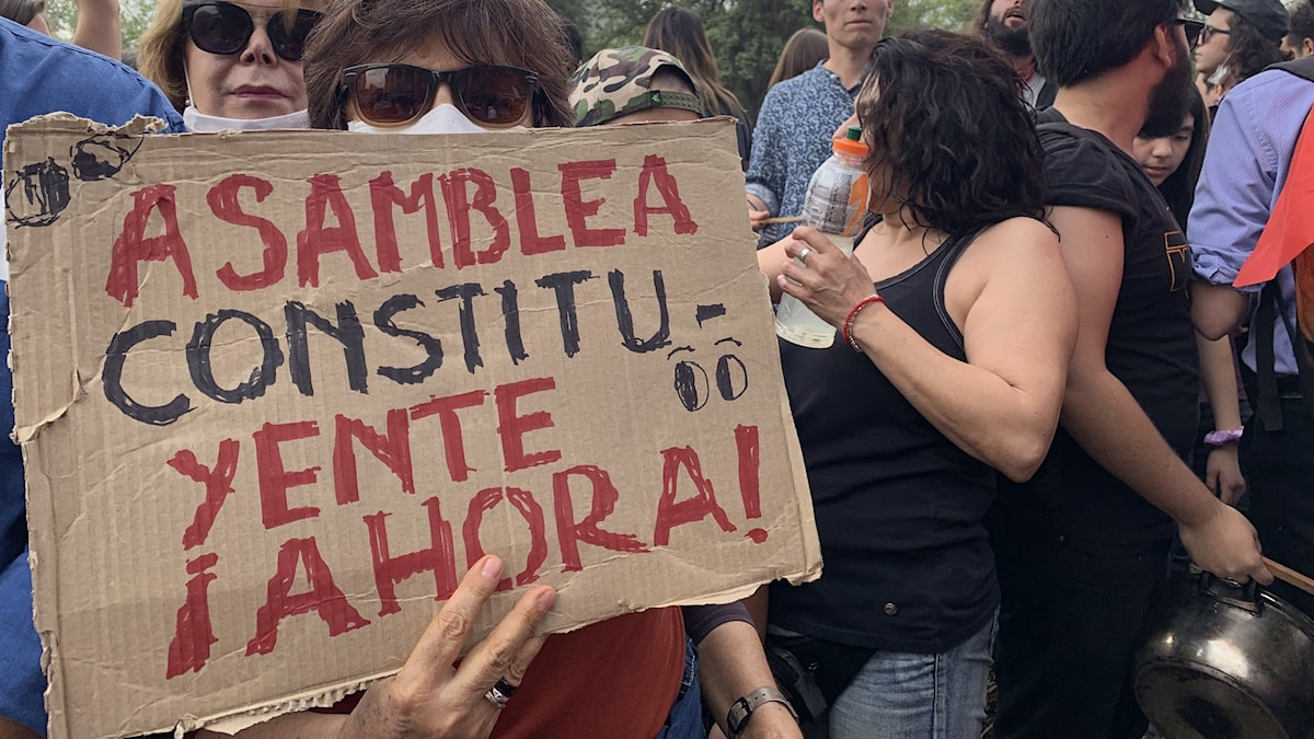 Angelica Fuentes bar på ett plakat med krav på en ny författning.