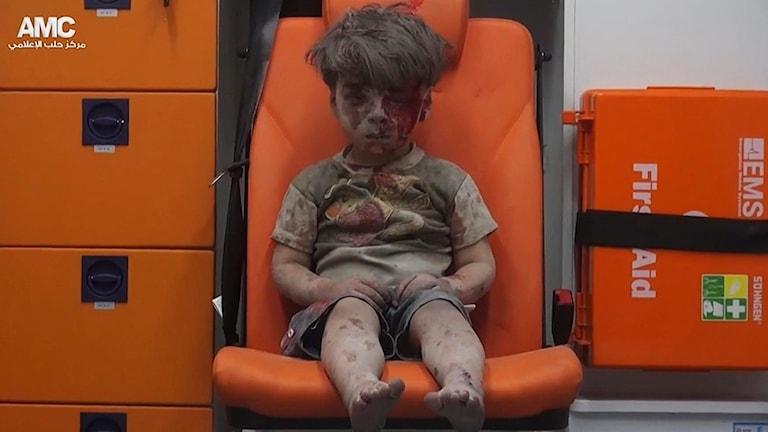 En femårig pojke täckt med blod och damm sitter längst bak i en ambulans.