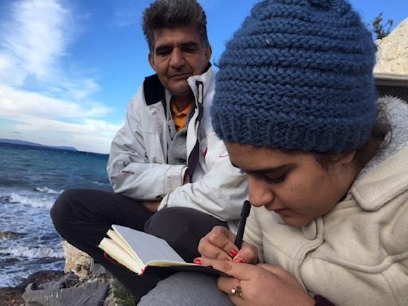 Mahsa skriver i en bok. hon och hennes pappa sitter vid vattnet i Turkiet och vill till Tyskland