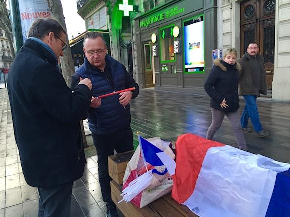 Christophe Lecomte säljer flaggor och skulle gärna se att fransmännen viftade lika mycket som amerikanerna. Foto:Beatrice Janzon/SR