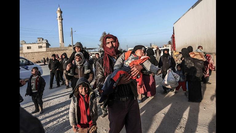 Människor flyr Syrien. En man bär ett litet barn.